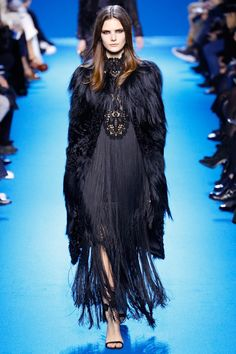 A model walks the runway at Elie Saab's fall-winter 2016 show wearing a fur coat with a fringe gown in black