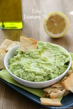 Easy Edamame Dip: 1 (12-ounce) bag frozen edamame 2 garlic cloves, peeled 3 tablespoons extra virgin olive oil 1 small lemon, juiced salt and pepper to taste 1 tablespoon fresh basil or cilantro (optional)