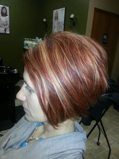 Dark copper hair color with bright blonde and copper highlights. Aveda color. Angled, stacked bob.