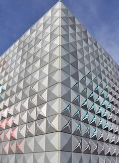 The seven and a half metre high facade of the storage depot  'Techno-Prisme' by London Architects Brisac Gonzalez in Aurillac, France, consists of 50×50 cm pyramidal aluminium panels that vary in colour and shape. The four different panel shapes vary slightly,  gradually opening in a bloom-like manner.
