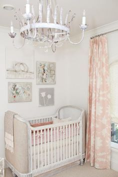Chic pink nursery features a linen upholstered crib, Restoration Hardware Baby & Child Belle Upholstered Crib, dressed in pink bedding placed under a collection of canvas art prints illuminated by a whitewashed French iron chandelier next to a window dressed in pink curtains, Mary McDonald Garden of Persia Blush Conch Fabric.