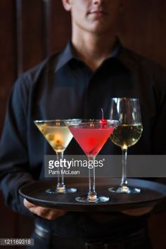 Stock Photo : Bartender holding tray of alchaholic beverages