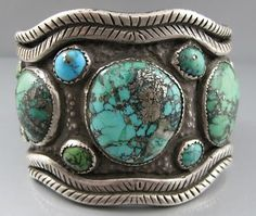 Ithaca Peak or Black Web Kingman Turquoise Sterling Bracelet Heavy and Strong…Bold and Impressive… Style: Very Likely Navajo Made Stone: Natural Ithaca Peak or Black Web Kingman Turquoise with Much Pyrite and Quartz Matrix Design Notes: Studio or Artist Piece, with a Stylized Outside Snake Banding. Saw-tooth Bezel Interesting Punch Back Type of Repousse This Bracelet … … Continue reading →