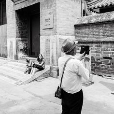 I saw this guy walking toward me and was hoping he would stop and do something interesting. He picked this spot where my kids were in the background and took a picture.  #China #streetphotography #street #story #storytelling #visualstorytelling #storyteller #blackandwhite  #Bnw #blackandwhitephotography #bnwlife #bnw_life  #documentary #documentaryphotographer #documentinglife #beijing #visitchina #hutong #stories #travel #traveldeeper #travelphotography #travelstoke #resourcetravel
