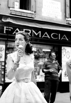 Maria Félix eating an ice cream in front of a pharmacy in Campo San Zulian. She's taking part in the Venice Film Festival. Venice, August 1959.