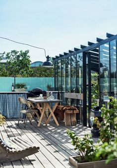 Beautiful terrace with an outdoor kitchen, wood furniture and installed awning.