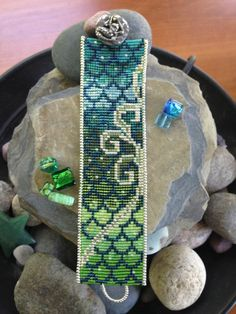 This one-of-a-kind original design is hand loomed in 11 colors of delica seed beads that fade from shades of turquoise to teals to greens. The beaded scales are splashed with sea foam in silvery loops and swirls that glint in the moonlight. It is bordered in silver rocaille seed beads and finished with a pewter mermaid button clasp from Green Girl Studios. It measures 7.25 inches long x 1 and 5/8 inches wide.