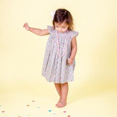 This gorgeous dress features hand smocked neck detail and a gathered bodice with angelic cap sleeves. We love the fresh pastels of this classic ditzy print.