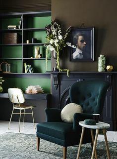 farbige wände dunkle farbtöne grüner sessel blumen regale
