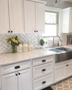 White kitchen, kitchen decor, subway tile, herringbone subway tile, farmhouse sink, stainless steel farmhouse sink, Rae Dunn, white cabinets, white backsplash, modern farmhouse, farmhouse Style, farmhouse decor, black hardware   See Instagram photos and videos from Robin Norton (@rock.n.robs)