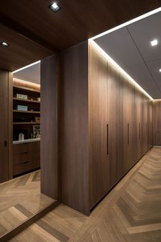 This modern walk-in closet has minimalist oakpaneling and doors, and a floor to ceiling mirror reflects the light throughout the space. #Closets #InteriorDesign #WoodFlooring