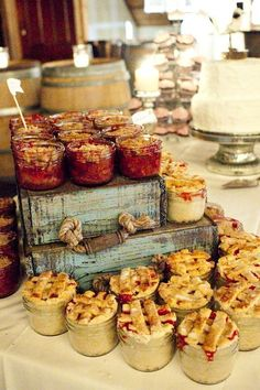 Rustic wedding dessert table with mini pies in mason jars