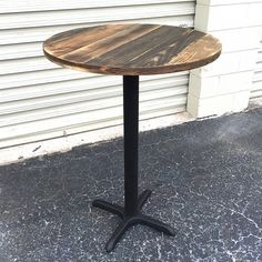 Made of reclaimed weathered pallet wood, this table top is set on a modern pedestal bar base Made to order The piece shown is show case only