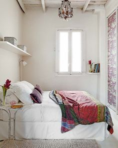 Pretty boho shabby chic bedroom. Bright bohemian throw, white washed walls & caged chandelier.