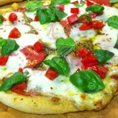 Home made pizza with whole wheat crust, pesto, heirloom tomato, fresh sliced mozzarella, red pepper and fresh basil. Yum!