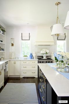 Summer decorated kitchen with a coastal vibe - blue and white striped rug, ginger jars and hydrangeas. #kitchen #kitchendecor #kitchenideas #summerdecor #blueandwhitedecor #kitchendecorating