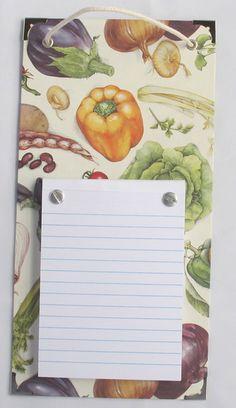Bloco de anotações em base de papelão, 13,5x28cm, preso com parafusos que permitem a troca do bloco. Bloco em papel branco, pautado, 10,5x14,5cm, 150 folhas com picote. Cantoneiras de metal nas 4 pontas. Cordão para pendurar. Base: revestida com papel e papel italiano. R$ 35,00