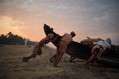 Fishermen pushing the boat out to see - Kollam, Kerala, India, 2009