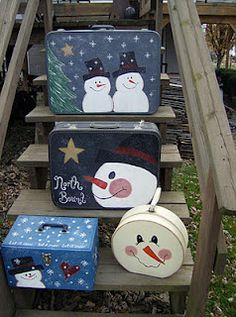 Snowmen painted on vintage suitcases.