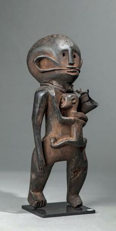 MATERNITY STATUE original wooden Zigoua Tanzania. She wears Under His left arm hung a horn to serve as That Was receptacle to medicine. Dark ...