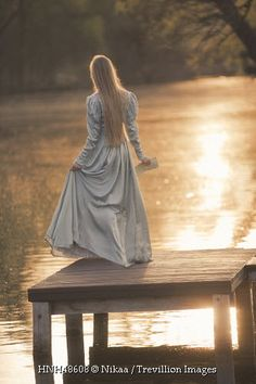 Trevillion Images - historical-woman-on-jetty-by-water