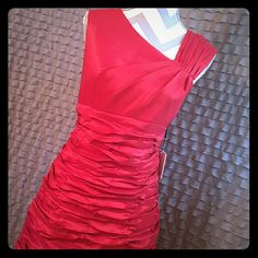 ROMANTIC Holiday Absolutely stunning red dress! Asymmetrical front and back with figure flattering ruching. Perfect for your next holiday party!  This dress features ruched detail and an asymmetrical neckline. A sleeveless cut and side zipper closure highlight the construction.   Shell: 61% polyester, 35% nylon and 4% spandex Lining: 90% nylon and 10% spandex   According to the Calvin Klein size guide Bust 40'' Waist 32.5'' Hip 43.5'' Does sit 2'' below natural waist Calvin Klein Dresses…
