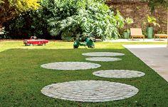 A viagem que os moradores desta casa fizeram para Bali e para a Tailândia serviu de inspiração para a arquiteta paisagística Michelle Simoncello Boccalato criar o caminho em formato de esferas que leva do portão de entrada ao jardim