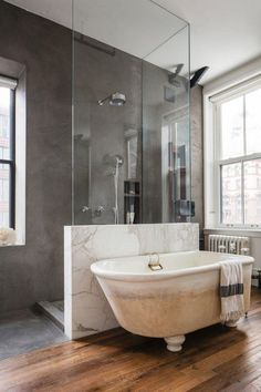 Modern meets traditional open floor plan bathroom with walk in marble and glass shower, gray plaster walls, freestanding bathtub and striped Turkish fouta towel hanging over the edge of the tub.