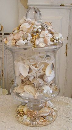 glass jar decorated with shells, old jewels, laces, etc