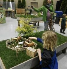 sod raised play table for kids.. farm, fence, horses, toys...THIS was at Seattle's Northwest Garden Show... the annual show is HUGE, kids are FREE, and they ALWAYS have a big play garden set up for kids... that year's play garden theme was Charlotte's Web (there was a petting zoo behind with FULL SIZED versions of Charlottes spun words like Humble and Some Pig)