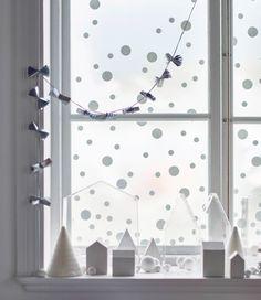 Ein mit einer Winterlandschaft dekoriertes Fenster, das sich aus kleinen Papphäusern, -bäumen und -schneeflocken zusammensetzt, u. a. gebastelt aus FIXA Bodengleitern.