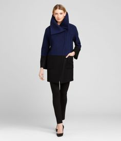 VALLORY COAT  Spoil yourself this fall with the Vallory coat crafted in a lush navy and black double face fabric. Asymmetric folds of material on the collar and a diagonal front closure add on-trend style touches. Fully lined with two large front pockets.