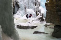 Walking on a frozen section of the Maligne River, Jasper National Park