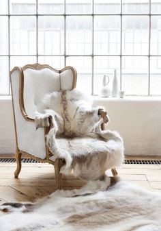 Snuggle up with a book in this white library chair, white throw and white animal print flooring.