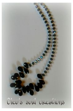 Envy is surrounded by black and glass Rondelle and briolette faceted beads.