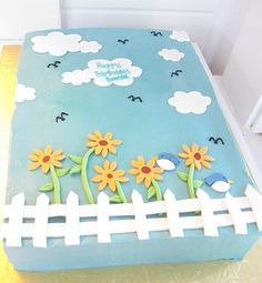 Blue birthday cake with clouds yellow daisies white clouds white fence and birds.JPG