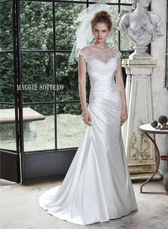 Demure illusion, accented with lace appliques, adorns the bateau neckline of this elegant Odara Crepe Back satin A-line wedding dress, with asymmetrical pleated bodice and dramatic illusion back, edged with lace appliques. Finished with covered buttons over zipper closure.  Maggie Sottero Bridal - 5MN691-Roxanne