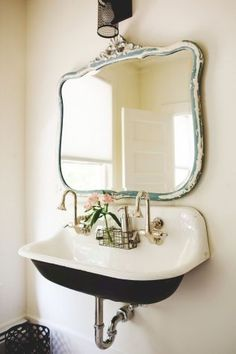 A cast iron trough sink provides the perfect look for a vintage farmhouse bathroom.