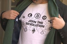 A man wears a T-shirt showing off several cryptocurrency logos. Latest Gadgets, Cryptocurrency, Menswear, Tech, T Shirts For Women, Logos, How To Wear, Fashion, Moda