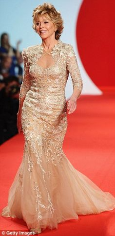 Still got it: Hollywood legend Jane Fonda walks down the catwalk in a gold couture creation at the Fashion For Relief show at the Forville Market at Cannes.