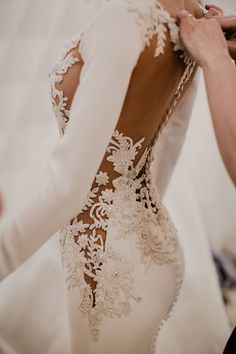 Model wearing a beautifully embroidered wedding gown with illusion lace details and fitted long sleeves // Before we reveal the 2018 Atelier Pronovias Collection, we're giving you an exclusive sneak peek backstage with these photos taken by our insider photographer Charlotte van den Berg. #weddingdress