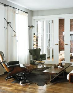 love the clean grey paint and white trim with the earthy furniture and brick wall. juxtaposition.