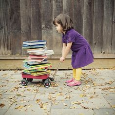 Little girl pulling a wagon full of books