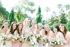 the bride and her bridesmaids in blush gowns at the racquet club reception holding their loose peach, blush and white bouquets of ranunculus, peonies, roses, spirea, tulips and greenery.