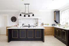 Stunning kitchen with timber, black and gold. Pearlised subway tile splashback is lovely too.