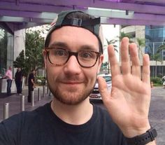 Dan Smith of Bastille in a stupid hat and his super cute glasses, waving, featuring his brilliant blue eyes