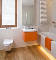 salle de bains avec sanitaire blanc, accents orange et carrelage de sol aspect bois