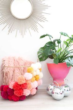 DIY Pom Pom basket. Pop of color and texture in mostly neutral room. Can purchase Pom Pom makers.