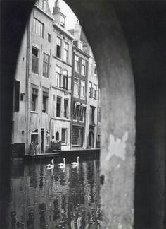 Een typische doorkijk op de Oudegracht aan de achterkant van de Rijnmarkt, waarin zwanen zwemmen, Utrecht, Nederland 1935.