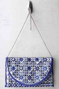 """Grab the Laguna Beige and Blue Embroidered Clutch and head out for margaritas! Shiny beige fabric is beautifully decorated with blue floral embroidery, mirrored beads, and crocheted trim. Lift top flap from the magnetic closure to access interior sidewall compartment. Carry as a clutch, or attach the 42"""" silver chain strap."""